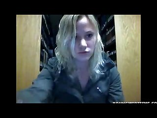 Pretty blonde teen striping in a public library