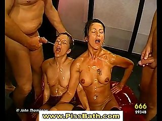 Two babes suck cock and get pissed on in watersports gangbang