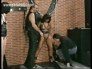 Horny slave with large metal clamps on her pussy lips and tied to wall is spanked by maste